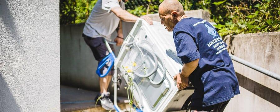 Die UmzugHelden beim tragen einer Waschmaschine für eine bessere Umzug Wien Erfahrung.