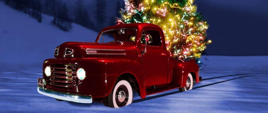 Roter geschmückter LKW transportiert einen Christbaum beim Umzug an Weihnachten.